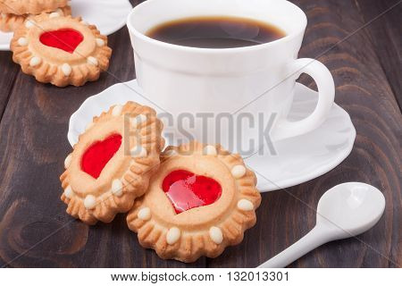 cookie with heart  jelly cup of coffee on  wooden table.
