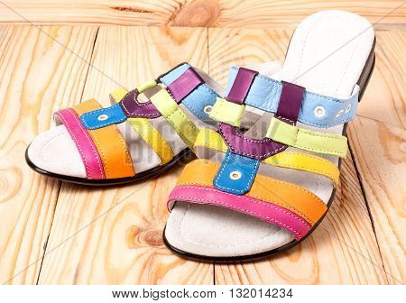 colorful female low-heeled sandals on a light wooden background.