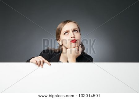 Portrait of puzzled businesswoman looking up above blank space