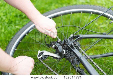 Man adjusts the derailleur bike. black moutain bike