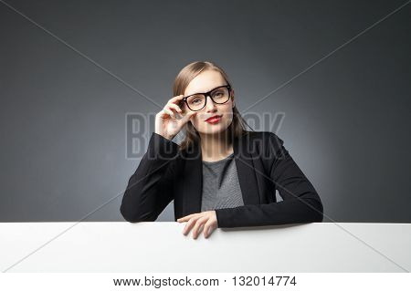 Portrait of beautiful businesswoman in glasses with red lips looking at camera