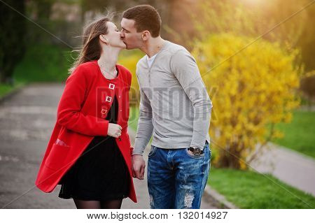 Loving Couple Walking And Kissed Near A Bush With Yellow Flower