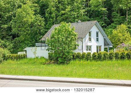 House / home with yard trees and bushes around - trees / forest in the background