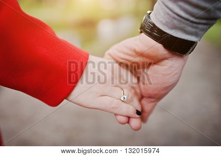 Close Up Hand In Hand With Engagement Ring Of Couple In Love