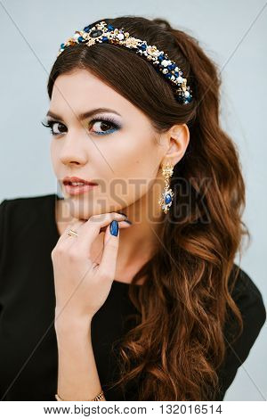 Street fashion portrait of beautiful woman with jewelry, jewelry with precious stones. Manicure and makeup in the same style blue, blue lacquer coating, blue jewelry