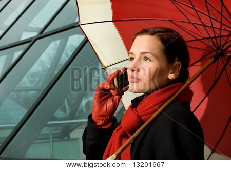 Beautiful brunette with red umbrella talking on the phone