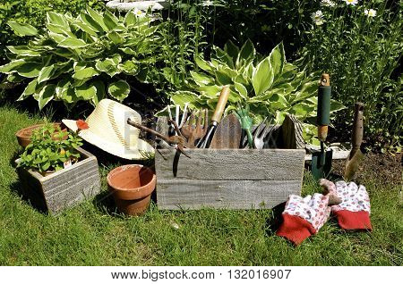 A gardener's box of tools, gloves, and straw hat are located next of a bed of plants .