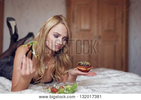 Blonde woman lying on bed eating salad and doughnut indoors