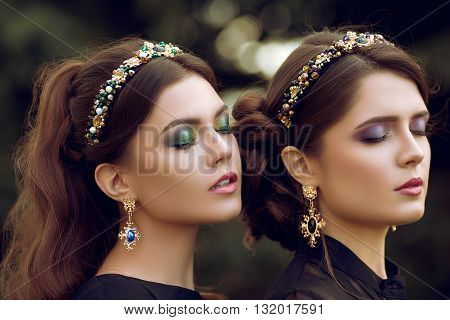 Two beautiful brunette women with a bright color makeup, jewelry, ring, earring, eyes closed. Close-up portrait of two girls with curly hair, hairstyles