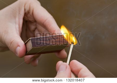 hands striking a match on blurred background closeup