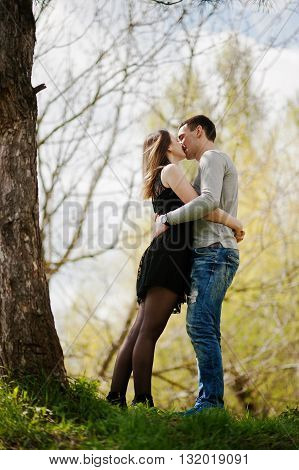 Happy Romantic Couple In Love Stay Near Tree And Kissing. Vertical Photo
