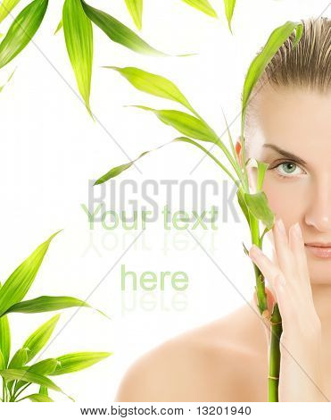 Schöne junge Frau mit einer Bambuspflanze