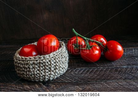 Jute basket with tomatoesvegetables on a brown background basket made of jute branch of red tomatoes