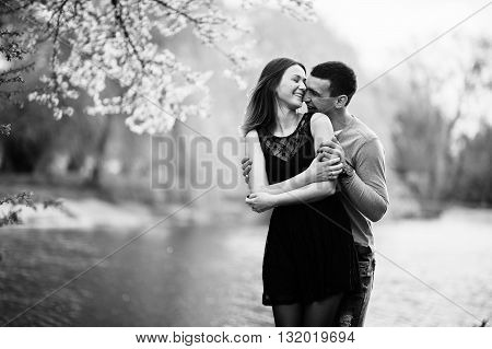 Young Couple In Love Outdoor. Laugh And Huggs Background Lake