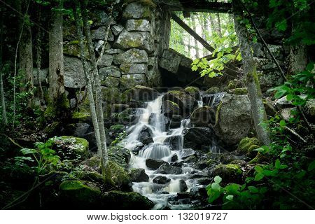 Small waterfall in deep forest, water coming from old ironworks.