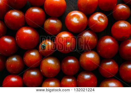Heap of cherry tomatoes ripe tomatoes cherry tomatoes on a wooden table