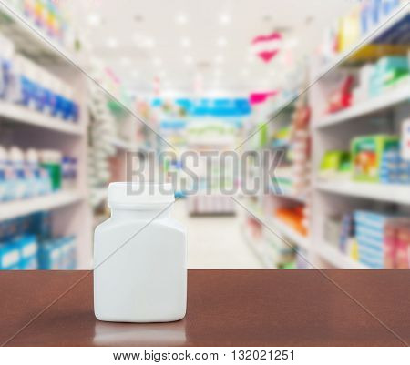 Pill bottle on table top on blurred pharmacy Pharmacy in shopping mall Pharmacy in shopping center Shoping drug and pill at pharmacy in holiday