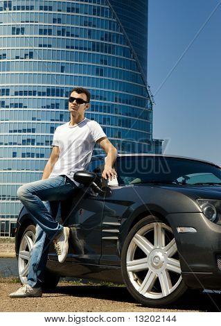 Guapo, de pie junto al coche del deporte moderno