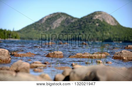 Summertime image of Acadia National Park in Maine with rocks mountains and water