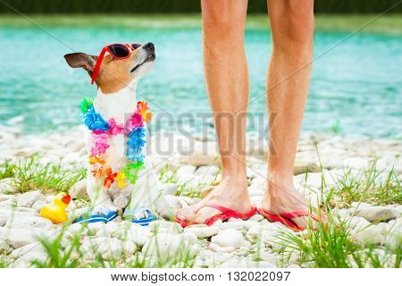 dog and owner close together at the beach on summer vacation holidays at ocean or river shore with sunglasses and flip flops