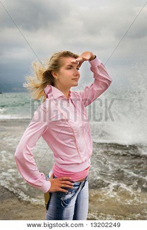 Hermosa joven en tormenta cerca del océano