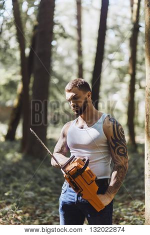 portrait of aggressive muscular male lumberjack woodworker with chainsaw in hand posing