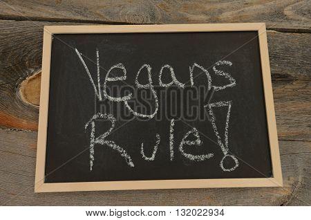 Vegans rule written in chalk on a chalkboard on a rustic background