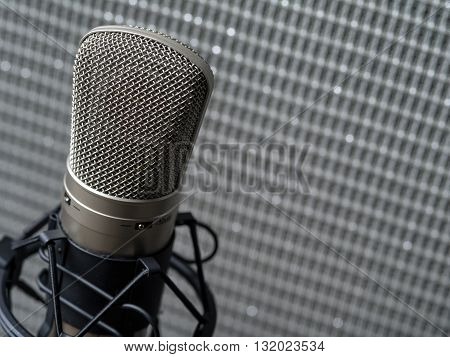 Photo of a large diaphragm studio condenser microphone in a shock mount in front of a guitar speaker cabinet.