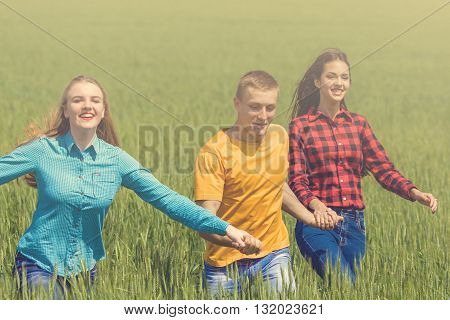 Young Happy Friends Running On Green Wheat Field