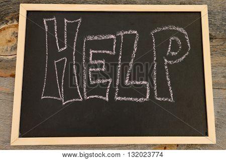 Help written in chalk on a chalkboard on a rustic background
