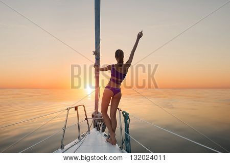 Girl standing on yacht bow. Lady on yacht raises hand. Sunrise in the Caribbean Sea. Happier than ever.