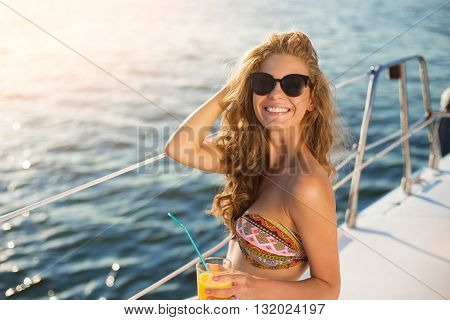 Smiling girl on yacht. Lady in suglasses holding drink. Cool drink and fresh air. Living a happy life.