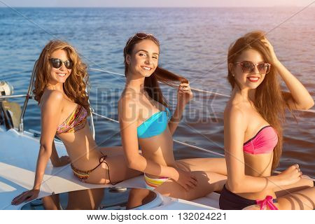 Smiling women on a yacht. Attractive girls on sea background. Bright sun and happy smiles. Positive mood and good health.