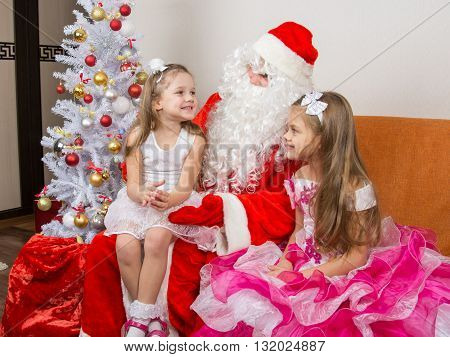 Little Girl Sitting On The Lap Of Santa Claus And Tells Poem