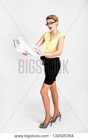 Young beautiful business woman in a black skirt and yellow blouse blonde goes with magazines