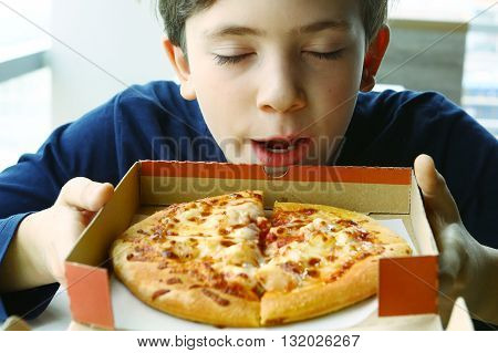 preteen handsome boy smell pizza in box close up photo