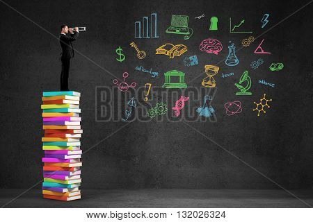 businessman standing on book and looking through a telescope