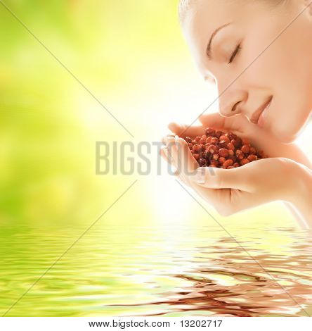 Beautiful young woman holding handful of fresh strawberries reflected in rendered water