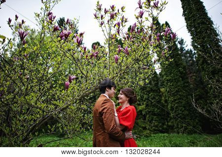 Couple Hugging In Love Near Magnolia Tree. Stylish Man At Velvet Jacket And Girl In Red Dress In Lov