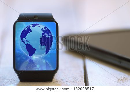 Smart watch on a white wooden table connected to a smart phone. Global communication symbol. Empty copy space for Editor's text.