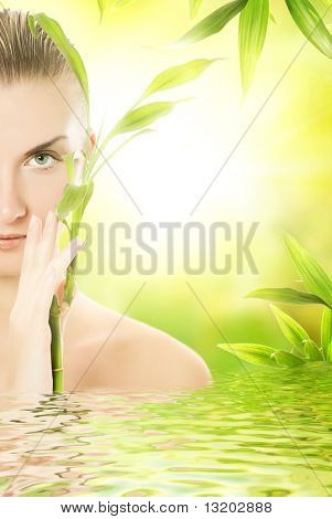 Beautiful young woman with a bamboo plant reflected in rendered water