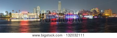 Cairo Egypt - May 26 2016: Panoramic view of the Island of Zamalek in central Cairo at night with it's famous boat restaurants on the Nile river.