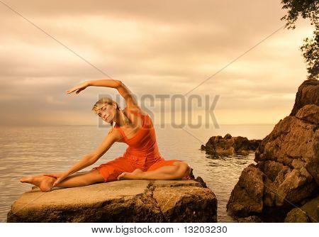 Bela jovem fazendo exercícios de ioga ao ar livre