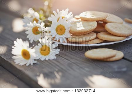 Camomile and cookies on a plate on a wooden table.