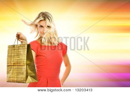 Beautiful young woman with a bag over abstract yellow background
