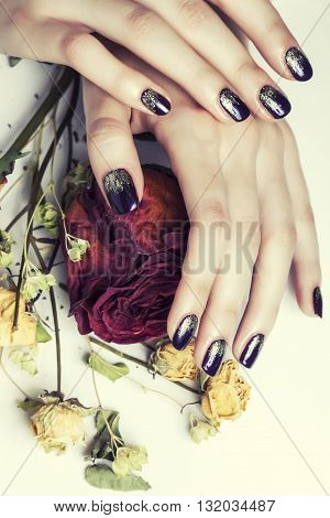 close up picture of manicure nails with dry flower red rose, dehydrated by winter, stylish woman fingers