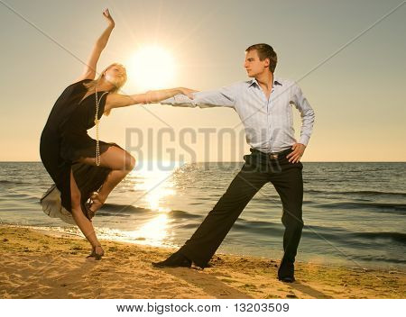 Beautiful young couple dancing tango on the beach at sunset