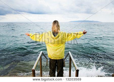Brave Woman Greeting Stormy Ocean splash raincoat