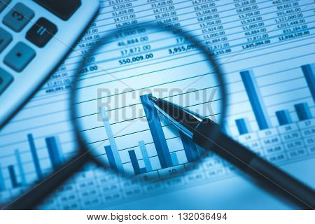 Business accounting spreadsheet with calculator and pen through magnifying glass in business blue, close up macro