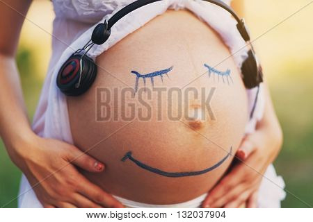 Pregnancy and music. Parenting, care, early development. Pregnant woman belly closeup with smiling funny face drawing. Happy pregnancy, fun, creativity. Art, Music therapy. Smile face at belly.